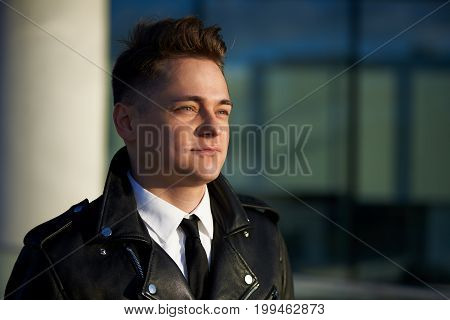 Headshot of fashionable young office worker or student with smooth face posing in urban setting looking into distance with positive dreamy smile planning summer vacations abroad by the ocean