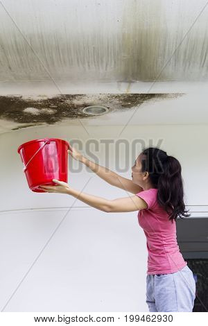 Portrait of Asian woman holding a bucket for collecting rainwater from damaged ceiling