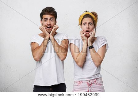 Portrait Of Emotional Surprised Young Man And Woman Keeping Eyes Popped Out And Holding Hands On The