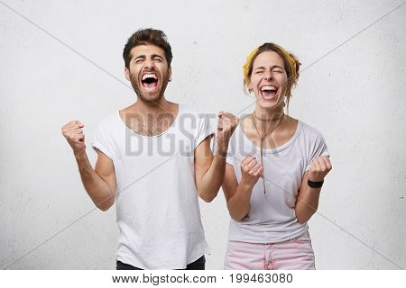 People, Happiness, Winning, Victory, Success And Good Luck. Indoor Shot Of Two Young Caucasian Peopl