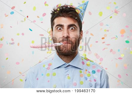 Portrait Of Bearded Man Who Is Celebrating His Birthday Party, Wearing Light Blue Shirt And Party Ca