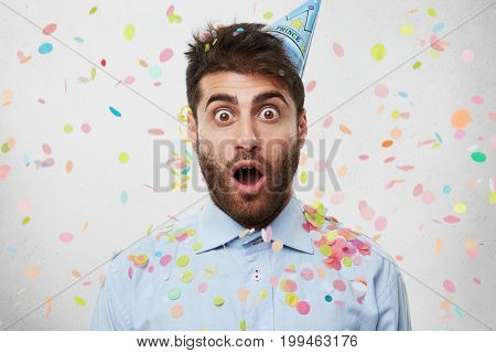 Young Caucasian Man Dressed In Formal Shirt And Having Party Cap On Head, Celebrating His Birtday, L