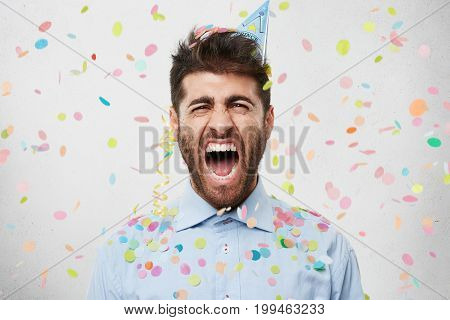 People, Celebration, Birthday Concept. Dissatisfied Bearded Man In Holiday Cap And Shirt, Screaming