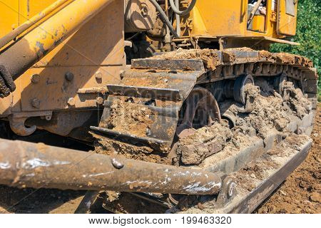 Close-up of the caterpillars or crawler of the large industrial bulldozer or excavator