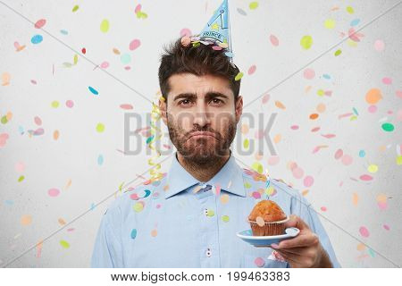 Upset Young Man Wearing Party Cap And Shirt, Holding Little Cake With Candle, Having His Birthday, C