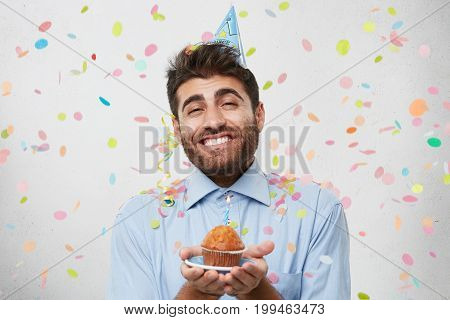 Excited Man With Stylish Hairdo, Hazel Eyes And Thick Beard, Smiling Broadly While Holding Little De