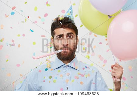 Indoor Shot Of Astonished Puzzled Guy Wearing Blue Shirt And Cone Hat On His Head Looking Surprised,