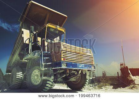 Yellow mining truck. Work industrial machinery, limestone mining. Sun light effect, toned. Copy space