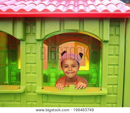 Smiling pretty little girl playing in a play house