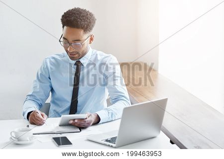 Successful Young Male Dark-skinned Accountant With Afro Hairstyle And Bristle Using Digital Tablet,
