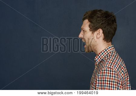 Profile portrait of young European man with bristle wearing checkered shirt shouting expressing indignation posing against blank studio wall background with copy space for your advertisement