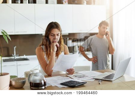Young Attractive Female Accounter Being Busy With Her Work At Home, Calculating Figures And Making B