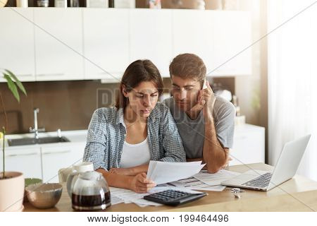 Young Bearded Man Chatting Over Smart Phone And Looking Attentively In Documents Which His Wife Keep