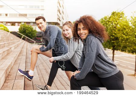 Group of multiethnic young people in sportswear exercising together on city stairs, stretching legs and looking at camera