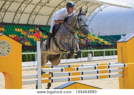 TAGANROG ROSTOV-ON-DON REGION AUGUST 6 2017: Competitions in equestrian sport devoted to the Day of Liberation of the Neklinovskiy district. Horseman on a speckled horse jumps over an obstacle on a background of spectators' grandstands close up