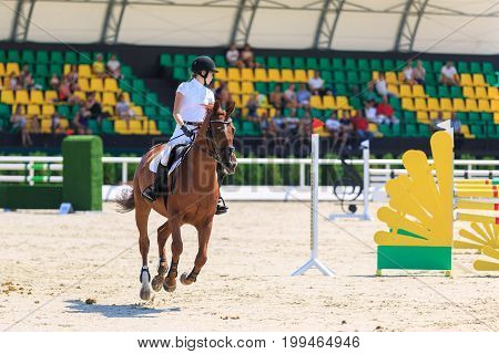TAGANROG ROSTOV-ON-DON REGION AUGUST 6 2017: Competitions in equestrian sport devoted to the Day of Liberation of the Neklinovskiy district. Young horsewoman rides on the chestnut horse on the background of the spectators' grandstands