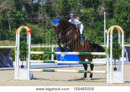 TAGANROG ROSTOV-ON-DON REGION AUGUST 6 2017: Competitions in equestrian sport devoted to the Day of Liberation of the Neklinovskiy district. Horsewoman in a white suit on horse jumps over the barrier