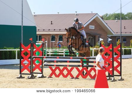 TAGANROG ROSTOV-ON-DON REGION AUGUST 6 2017: Competitions in equestrian sport devoted to the Day of Liberation of the Neklinovskiy district. Horseman on a chestnut horse jumps over a red barrier