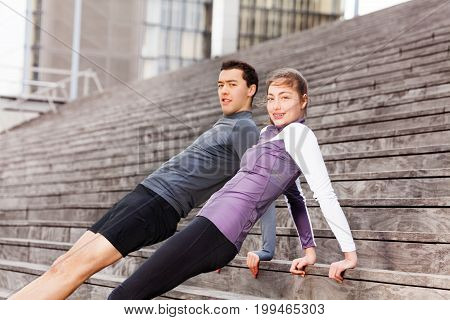 Close-up portrait of sporty young couple holding reverse plank position, exercising together outdoors on city stairs