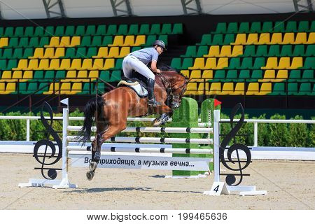 TAGANROG ROSTOV-ON-DON REGION AUGUST 6 2017: Competitions in equestrian sport devoted to the Day of Liberation of the Neklinovskiy district. Chestnut horse with a rider jumps over the barrier against the background of the spectators' grandstands