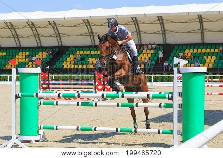 TAGANROG ROSTOV-ON-DON REGION AUGUST 6 2017: Competitions in equestrian sport devoted to the Day of Liberation of the Neklinovskiy district. The rider on the chestnut horse jumps over the green barrier close-up