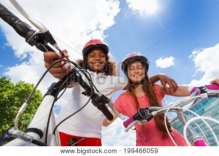 Low angle portrait of two preteen girl-friends standing with their bicycles against cloudy sky