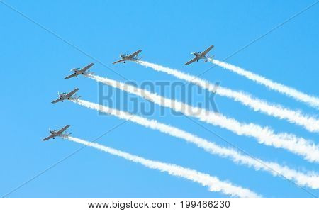 Group Of White Turboprop Aircraft With A Trace Of White Smoke Against A Blue Sky