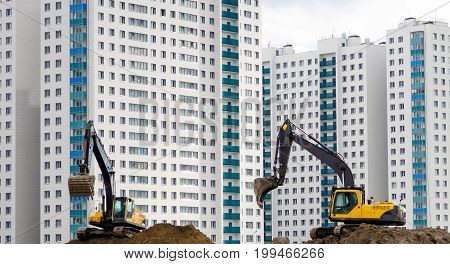 Excavators work on the sand on the background of multi-storey houses