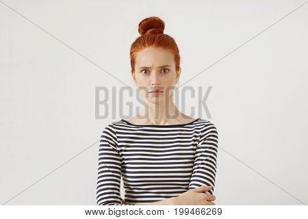 Serious Female Model With Reddish Hair Tied In Bun, Standing Against White Background In Casual Swea