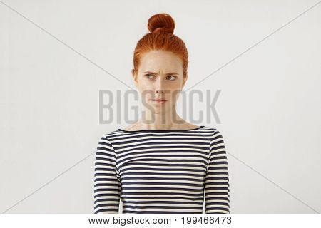 Pensive Redhead Woman With Hair Bun, Curving Her Lips And Raising Eyebrows While Thinking Over Or Ma
