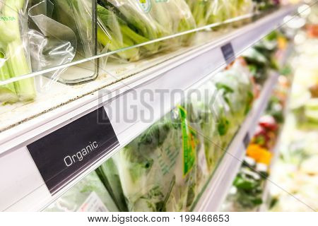 Organic Food Signage On Modern Supermarket Vegetable Aisle