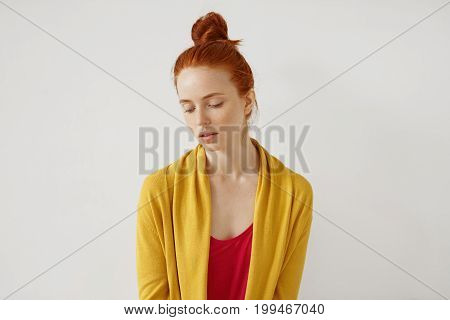 Calm Woman With Freckled Skin, Bright Ginger Hair, Wearing Red T-shirt And Yellow Cape, Looking Down