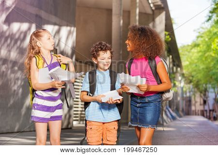 Group of kids with paper sheets talking standing near school entrance and looking at each other