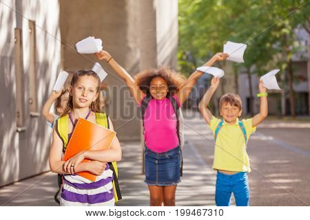 Happy diverse group of kids standing near school with lifted hands and papers