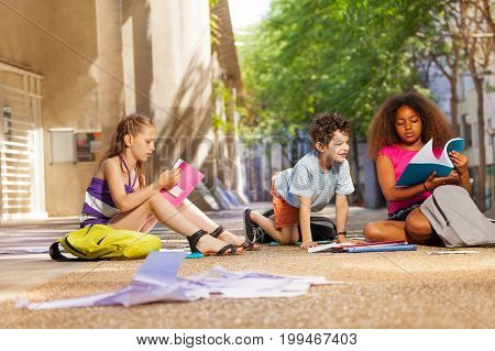 Group of kids reading books and textbooks on the ground near the school