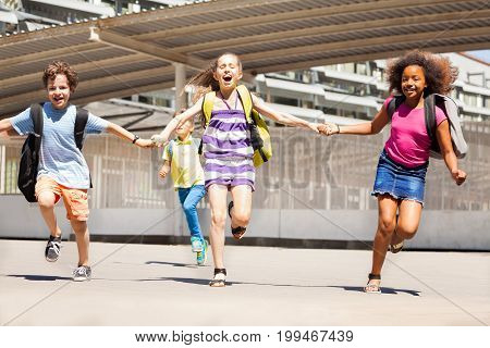 Girls and boys running to school scramming happy looking to camera