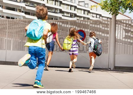 Group of children run to school wearing backpacks view from behind
