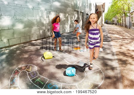 Group of kids play hopscotch near school jumping one after another