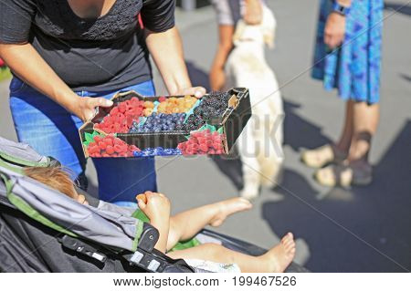 Woman Buying A Box Of Fresh Berries At The Farmers' Market.