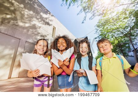 Group of four kids stand with papers near the school smiling to the camera