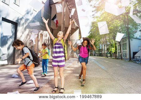 Group of friends schoolkids throwing paper sheets in the air with excitement and lifted hands