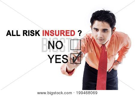 Image of young businessman using a pen while choosing a yes option on the whiteboard with text of all risk insured