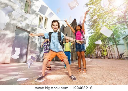 Handsome boy with happy vivid expression and spread hands, friends throw paper sheets in the air on background