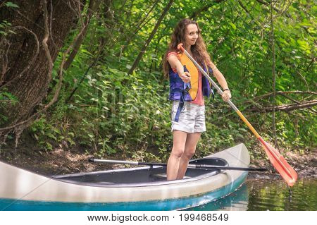 A young girl showing direction on a kayak with a paddle in a forest on a stream with lianas