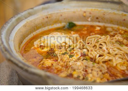 Abstract smoke on Tom Yum Kung with noodles and seafood popular Thai food. Tom Yum Goong Spicy Sour Soup on wooden table top view Thai local food