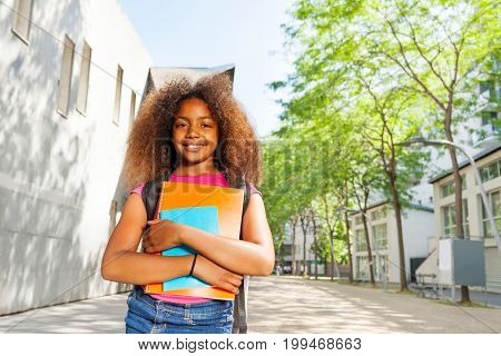 Close nice portrait of a African girl with textbooks near school