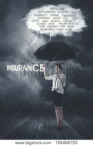 Pretty businesswoman writing a text of insurance and holding umbrella under a cloud bubble of problems