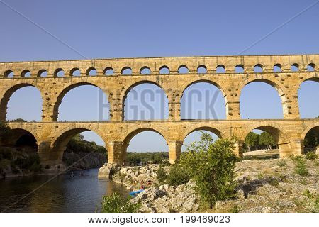 NIMES, FRANCE - August 18, 2012: People near the famous landmark ancient old double arches of Roman aqueduct of Pont du Gard, Nimes, France