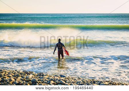 Surfer go to surf at sunset or sunrise. Surfer in ocean and waves