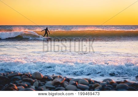 Surfer ride on wave at warm sunset or sunrise. Surfer in ocean and waves